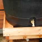 handmade stand for rain barrel for easy dispersing of collected water