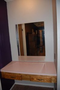 Old bathroom vanity with pink formica counter